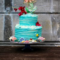 Mermaid Buttercream cake with an Isomalt cake board and hand and sea shells. no molds.