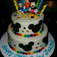 Mickey And Friends a small stacked cake. M&M polka dots, fondant mickey head silhouettes, gum paste streamers and toy figurines.