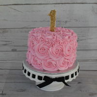 "Pink Rosette Smash Cake   Pink rosette smash cake with a ""1"" topper covered in gold sprinkles. We also made some matching cupcakes."
