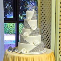 Silver And White Wedding Cake A 5-tier wedding cake consisting of mixed flavours, all iced with fondant and decorated with silver multi-sized cachous and white gum paste...