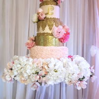 Suspended Cake 4 tiers cake and one layer of gold glitter covered styrofoam. Iced with a pale pink buttercream and finished with gold fondant accents. It...