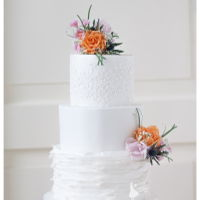 White Ruffled Weddingcake With Orange And Pink Flowers Serene white weddingcake with sugarflowers.