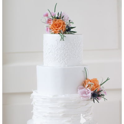White Ruffled Weddingcake With Orange And Pink Flowers