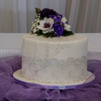 """60 Plus Anniversary Cake"" Purple gum paste Rose with white filler flowers and LilacsRose Lace around and falling unto the board and a Lace drape with the bouquet."
