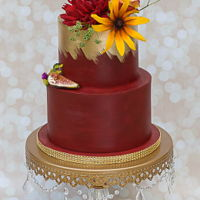Burgundy And Gold Cake was wrapped in modeling chocolate, then painted to give it a more rustic feel. The gold was luster dust + lemon extract that was...