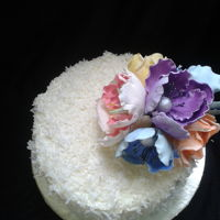 Buttercream Cake Pina colada cake decorated with coconut shavings and sugar flowers