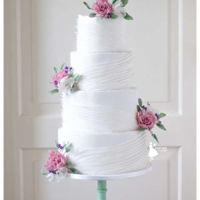 Classic With A Modern Twist A classic looking wedding cake with modern ruffled drapes.With handmade sugarflowers to complete it.