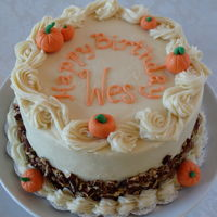 Fall Birthday Eight inch round carrot cake in cream cheese icing with modeling chocolate pumpkins and toasted pecans.