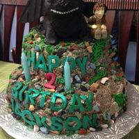 "How To Train Your Dragon Cake Two tier ""mountain"" covered in buttercream with chocolate rocks. Rice krispie treats dragon covered in chocolate clay. Figurine..."