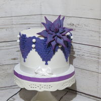 Purple Lace/succulent Cake This is a Noir Chocolate Cake with chocolate SMB and fresh raspberry preserves. Fondant covered with lace and fondant/gumpaste succulent....