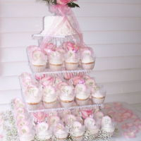 Wedding Cupcake Tower   white cupcakes with pink sugarged rose petals on plexiglas seperators with wine glass pillars. Lights inside wine glasses
