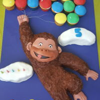 Curious George made out of vanilla buttercream and fondant. balloons are cupcakes.