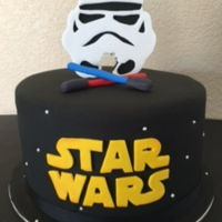 Star Wars Cake Star Wars logo with stars, lightsabers, and a stormtrooper topper.