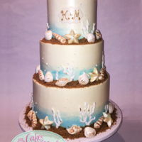 Beach Themed Wedding Cake   IMBC cake with chocolate shell accents and brown sugar as sand. Piped coral with royal icing.