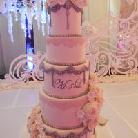Blush Pink 5 tier wedding cake embellished with ornate silver moulds, edible pink lace and clusters of blush pink and ivory sugar flowers.