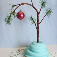 "Charlie Brown Christmas Tree Cake Charlie Brown's tree sweetly wrapped in Linus' blanket made from cake and fondant. Cake is an 8"" round layer with a 6""..."