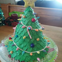 Christmas Tree Cake A foot tall christmas tree cake with a ten inch base covered in fondant leaves, lights, jingle bells, candy canes, gumball ornaments, and...