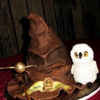 "Harry Potter Sorting Hat Birthday Cake   Sorting Hat of cake with fondant. Hedwig is RKT with fondant. Gumpast wand and edible image ""banner"". Cakepop golden sneech."