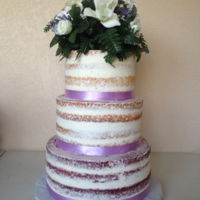 "Naked Wedding Cake  This is a 12"", 10"", and 8"" round cake. Just a simple buttercream. Trimmed with material ribbon. The topper was made by the..."