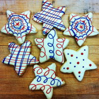 Patriotic Star Cookies   Patriotic star sugar cookies dipped in white chocolate decorated in dyed white chocolate.