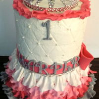 Pink & Gray 1St Birthday Small 3 tiered cake sits on top of over turned colander that is covered in fondant.