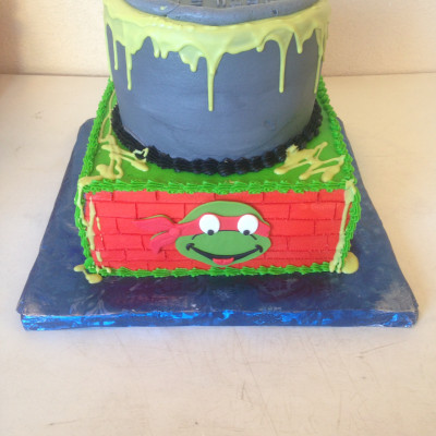 Teenage Mutant Ninja Turtles  This is a 10' square and 8' round cake. It's frosted in Buttercream. The faces are made out of Fondant. The ooze is Lime...