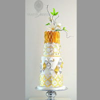 Cake With Origami Gold And Silver White 4 tier cake with Clematis on top, decoration origami, herringbone tesselation, weaving and folding in gold and silver cake lace