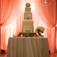 Elegant Ivory Gold Wedding Cake This elegant wedding cake was decorated with Ivory tiers and Gold leaf accents, a flowered tier and an Ivory/Blush pink Pomander topper....