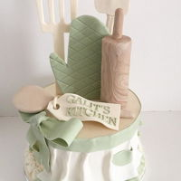 Kitchen Bridal Shower Cake Kitchen themed bridal shower cake with fondant apron, rolling pin, oven glove, spatulas, and wooden spoon.