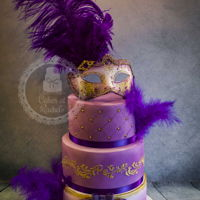 Masquerade Ball Cake  Three tier purple and gold masquerade themed cake, all lemon flavour, with quilting, beading, royal icing pattern, and topped with a...
