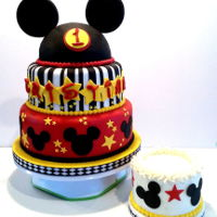 Mickey Mouse Themed 1St Birthday Cake And Smash Cake Mickey mouse themed, marshmallow fondant covered, 1st Birthday Cake with smash cake in buttercream with fondant decorations.