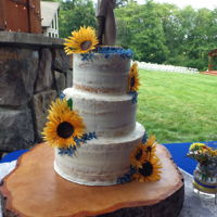 Naked Wedding Cake With Sunflowers 3 tiered white wedding cake, with minimal white buttercream. Decorated with wafer paper sunflowers and blue blossoms
