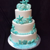 Ocean Themed Sweet 16 Cake Three tier cake in buttercream and airbrushed teal chocolate sea shells
