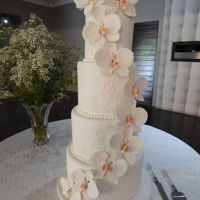 Orchid Crazy An elegant 4 tier wedding cake adorned with a cascade of handmade gumpaste Phaleanopsis Orchids. A simple royal icing piped pattern and a...