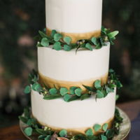 Eucalyptus, Fig And Olive Leaf Cake A gold brushed cake adorned with gumpaste eucalyptus, gumpaste olive leaves, gumpaste berries and real figs