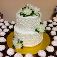 White Scroll Wedding Cake And Cupcakes All buttercream. Artificial flowers.