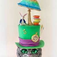 Alice In Wonderland Alice in Wonderland Cake with Cheshire cat sculpted cake tier and Alice sitting on a Mushroom.