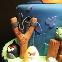 Angry Birds Head is rice cereal treats covered in chocolate and fondant; fondant over buttercream; fondant/gumpaste figurines