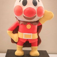 Anpanman (Japanese Character)Cake Sculpted, three flavor, standing figure cake. Hands and legs made with modeling chocolate. Head and torso all cake.