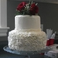 Blossom Wedding Cake 2 layer, white wedding cake. Smooth top layer. Bottom layer covered in blossoms. Bouquet of real red roses as the topper