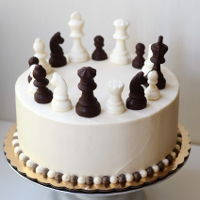 Chess Cake With Handmade Chocolate Chess Pieces chess cake with handmade chocolate chess pieces - vanilla cake filled with fresh whipped cream and pineapple, and covered with buttercream...