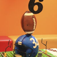 Football Theme Cake The football helmet and the ball are both vanilla cake with buttercream and chocolate ganache. The number 6 is made with pastillage.