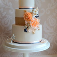 Maggie A pretty bouquet of peachy rose, dahlias, brunia and viburnum berries decorate this cake, trimmed with hessian for a rustic influence and...