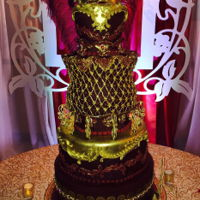 Masquerade Themed Cake Burgundy and gold! Power color combo for the adventurous at heart! Created by using several techniques, stenciling, carving, hand piping,...