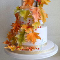 Melissa An autumnal wedding cake decorated with falling sugar leaves in varying shades, berries and gold accents