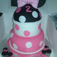 Minnie Mouse 2 Tier white almond cake with almond flavor buttercream and covered in fondant with handmade Minnie ears topper....