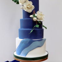 Navy Blue Wedding Cake White gum paste roses on navy blue with some greenery and bronze accents