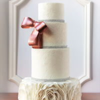 Rose Gold Bow And White Ruffles A lemon pound cake with raspberry filling wedding cake. The rose gold bow , embossed design and ruffles matched with the brides wedding...