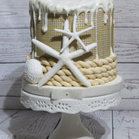 Seaside/burlap Cake This is a vanilla bean cake with dark chocolate ganache and raspberry preserves. The cake is covered i fondant and Cake Lace.Embellishments...