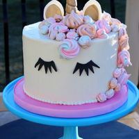 Unicorn Cake Frosted with Swiss Meringue Buttercream, Gumpaste horn, ears and eyelashes. Decorated with rainbow meringues.